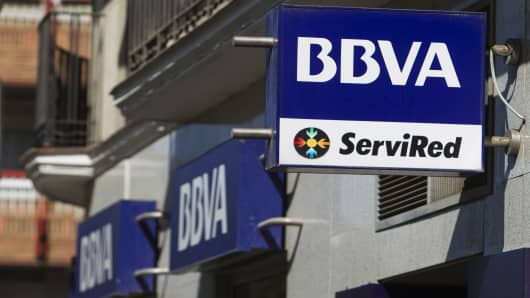 Signs sit outside a Banco Bilbao Vizcaya Argentaria SA (BBVA) bank branch in Madrid, Spain.